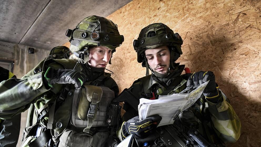 En kvinnlig soldat (tv) i full stridsutrustning under övning i markstrid i stadsmiljö. Kvinnliga och manliga rekryter övar lågintensiv strid vid markstridsskolan i Kvarn utanför Borensberg. Militär grundutbildning.