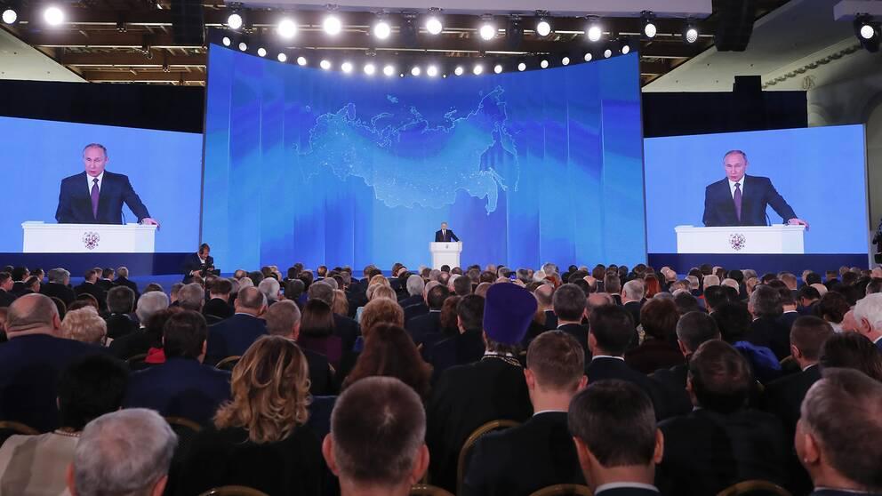 Rysslands president Vladimir Putin håller tal inför en stor publik.