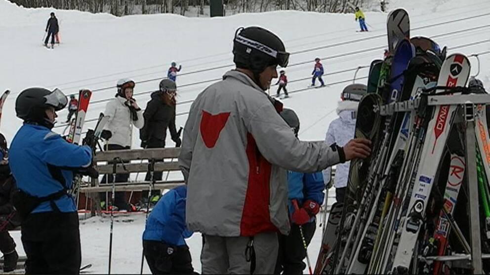 Skidåkare plockar skidor från skidställ