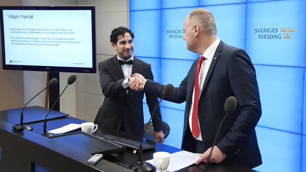 Civilminister Ardalan Shekarabi och Vänsterpartiets ledare Jonas Sjöstedt skakar hand vid en presskonferens.