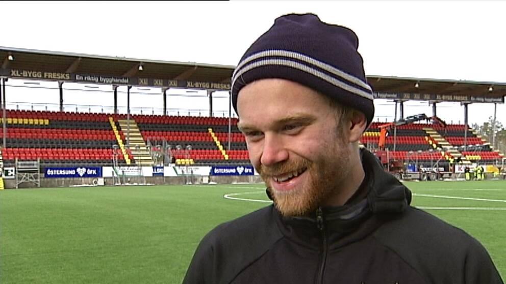 Leende Dennis Widgren stående på fotbollsplanen
