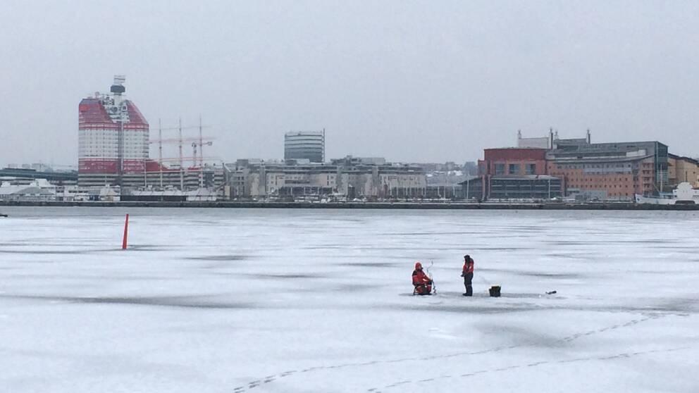Vintervy, snö och is vid Göteborgs skyline från Hisingen sett, med läppstiftet i horisonten, två personer pimplar ute på isen.