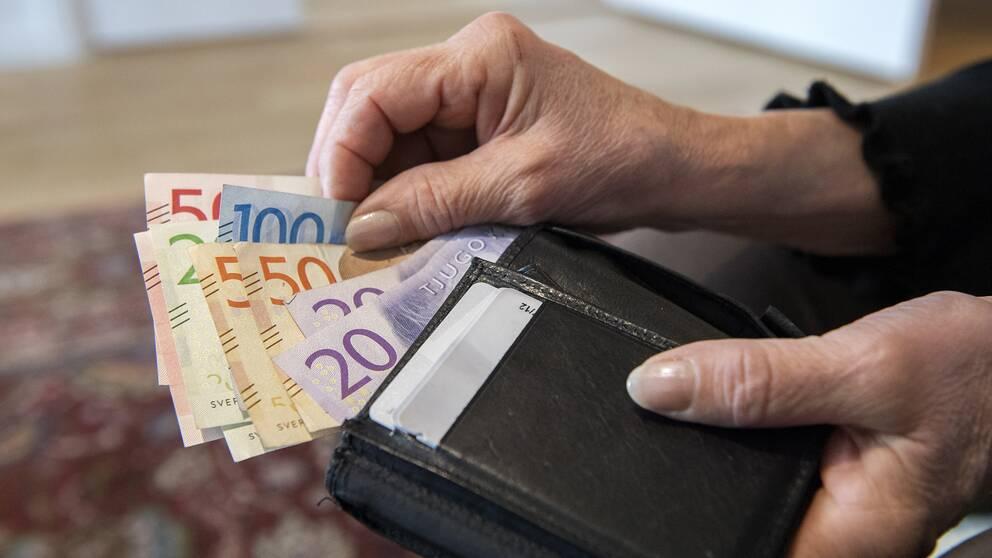 En kvinna håller i en plånbok med sedlar.