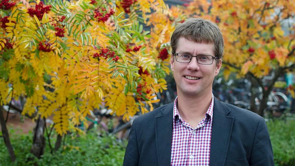En bild på en man i kostym framför ett träd.