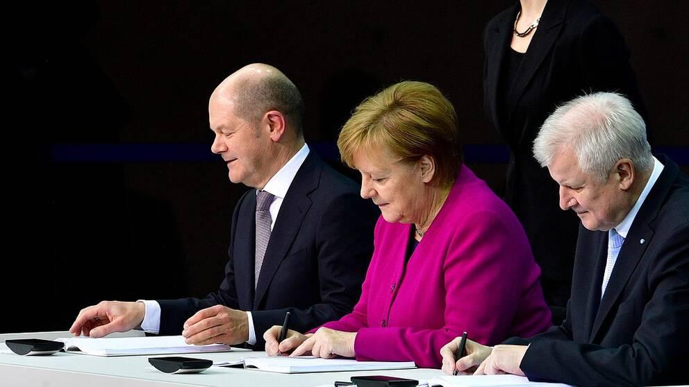 Angela Merkel skriver under regeringsförklaringen med finansminister Olaf Scholz (SPD) till vänster och inrikesminister Horst Seehofer (CSU) till höger.
