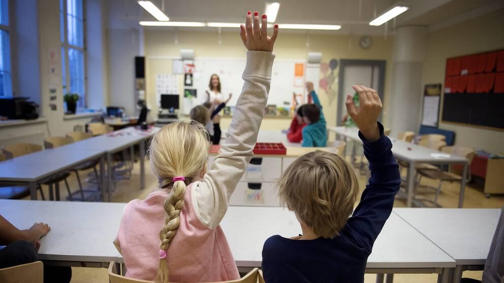 Barn i ett klassrum som räcker upp sin hand.