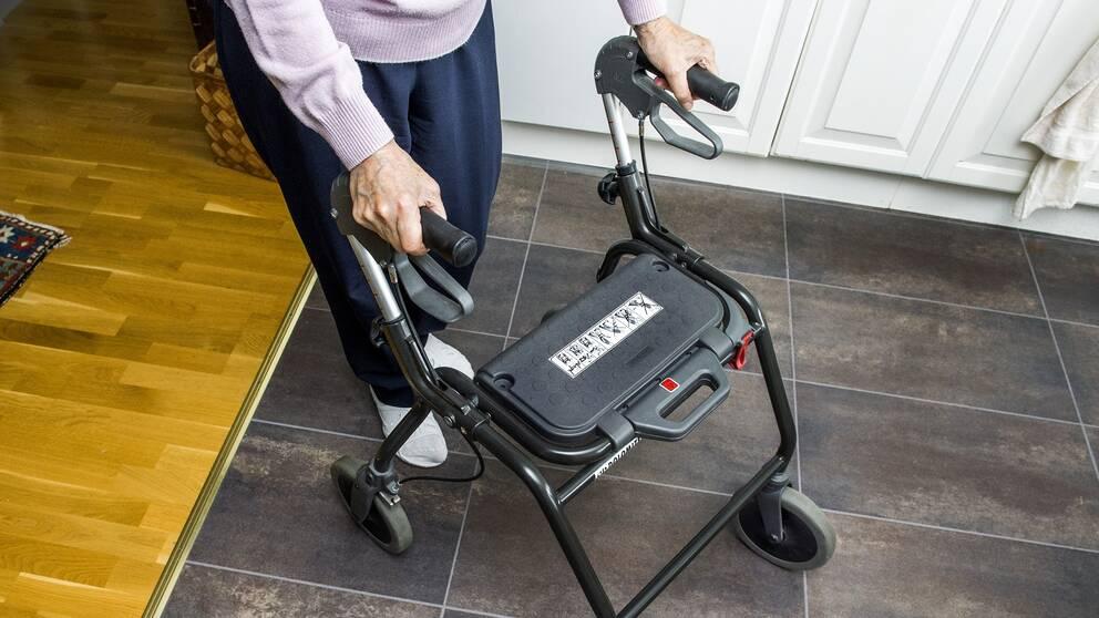 Äldre kvinna går med rollator
