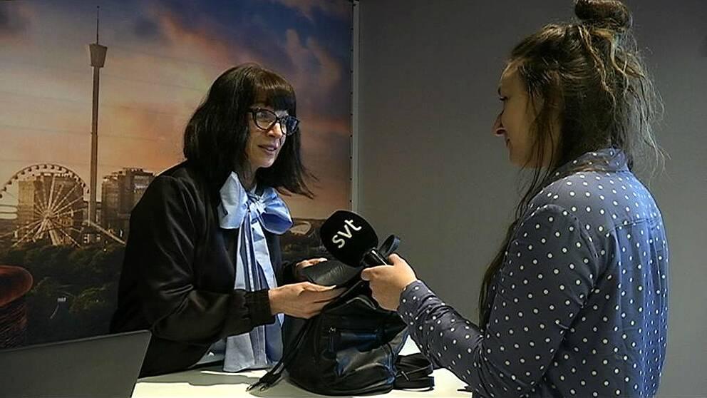 Väskexperten Malin Sveholm från Antikrundan undersöker en svart ryggsäck som tillhör SVT:s reporter Josefine Olausson