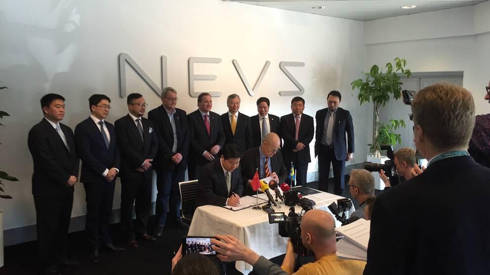 Stefan Tilk, vd på Nevs och Mr Jianghua Su, en av GSR Capitals ordförande skriver under ett samarbetsavtal med medarbetare, samt Stefan Löfven i bakgrunden.