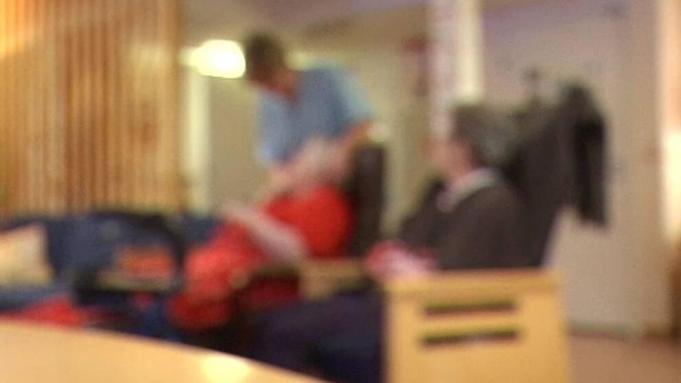 Bild i oskärpa med två äldre som får vård.
