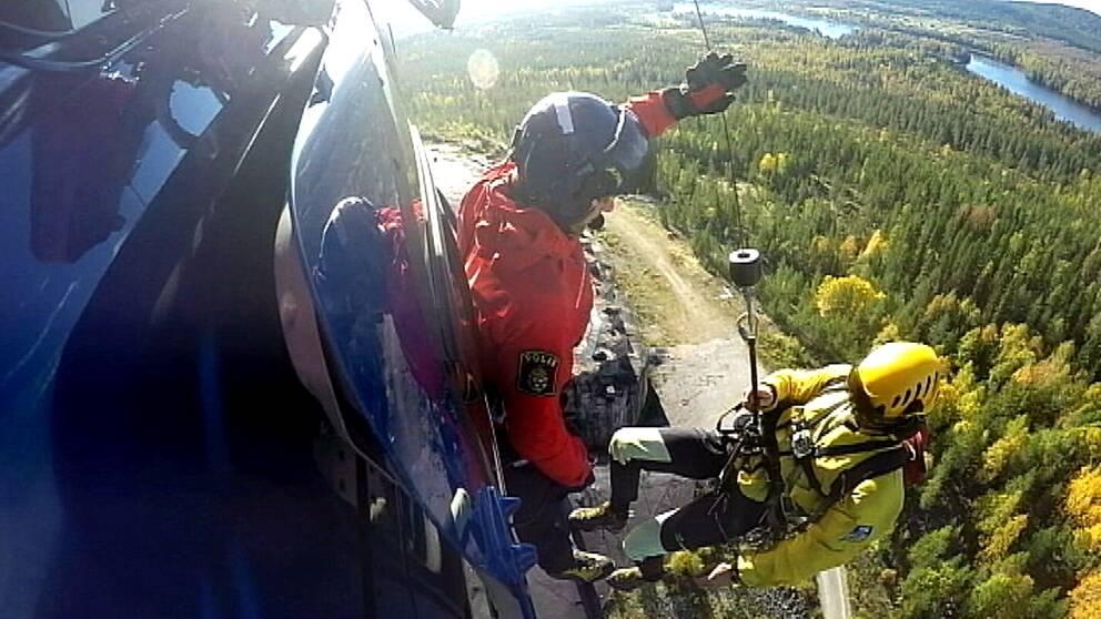 fjällräddare i polishelikopter firas ner i vajer