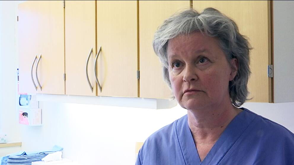 En kvinna i vårdkläder står framför en arbetsbänk.