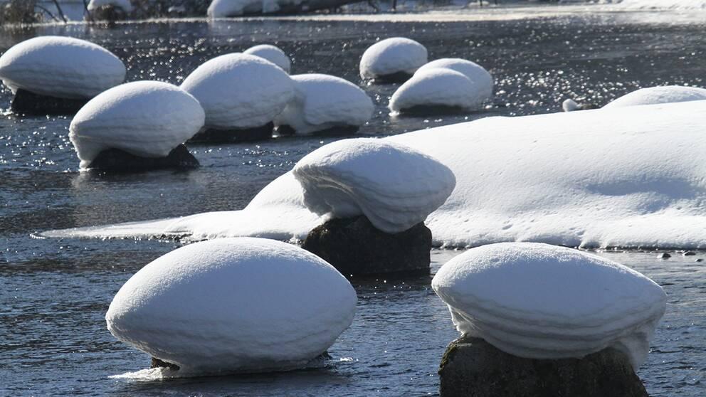 Rinnande solblänkande vatten tillsammans med snö och is i Lycksbäcken utanför Lycksele i södra Lappland