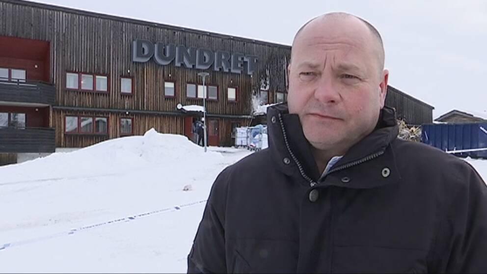 En man blir intervjuad framför en mörk och brandskadad byggnad.