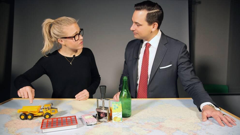 Två personer vid ett bord med olika saker, exempelvis en leksaks-lastbil.