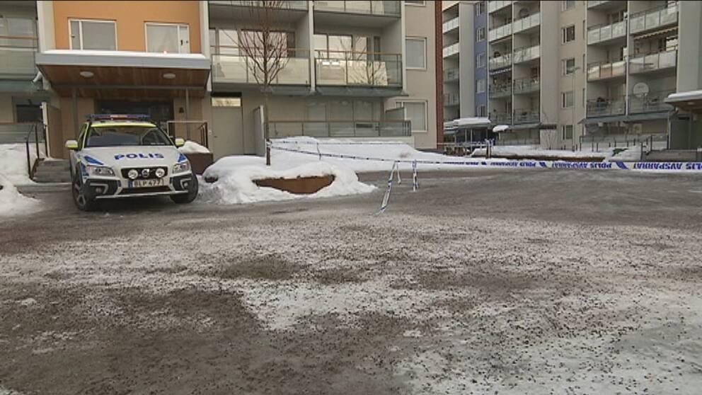 polisbil utanför lägenhetshus