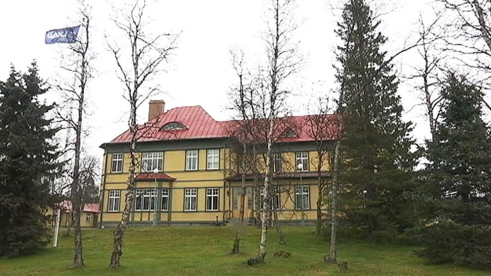Ett gult hus med massa fönster bakom träd och granar. En flaggstång vid sidan av huset.