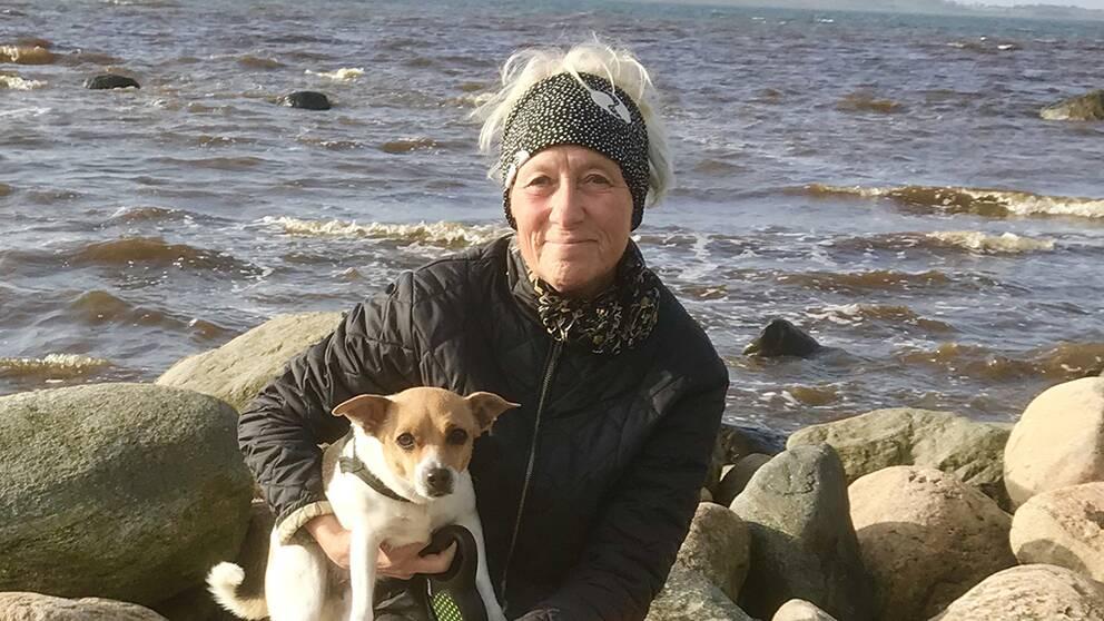 En kvinna sitter på klippor framför havet. I famnen har hon en hund.