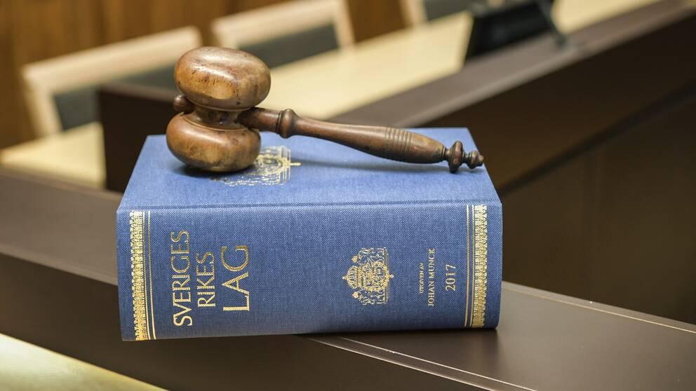 lagbok och klubba på bänk i rättssal