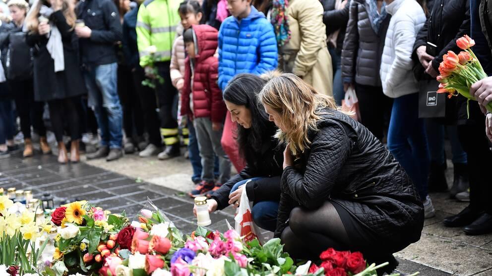 Två kvinnor står hukade framför ett blomsterhav för att hedra de som drabbades av terrorattacken på Drottninggatan i Stockholm 2017