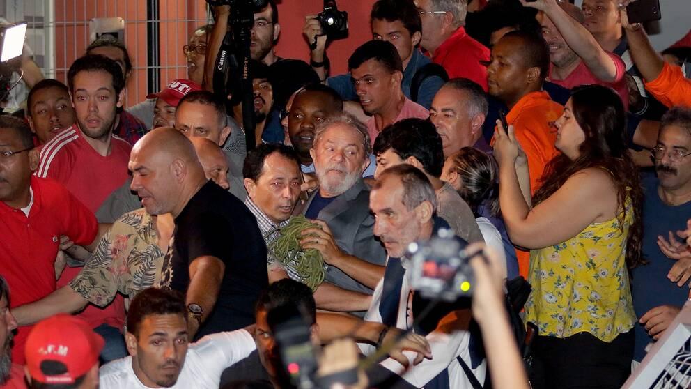 Här lämnar Lula da Silva (mannen med skägg och grå kavaj i mitten av bilden) metallarbetareförbundets högkvarter för att överlämna sig själv till polisen.