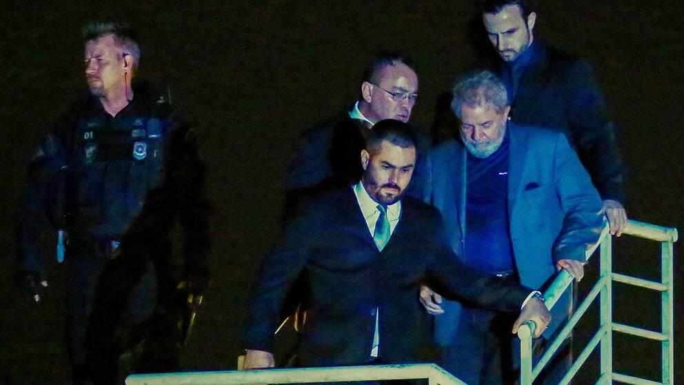 Lula da Silva överlämnade sig själv och anlände till polisen (iförd grå kostym) under lördagen.