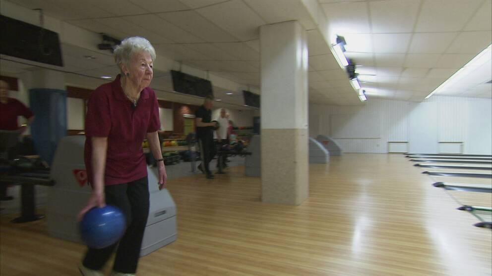 gammal kvinna med bowlingklot i handen, vid bowlingbana