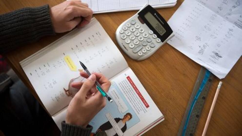 Bild på ett barn som sitter med en lärobok och en miniräknare.