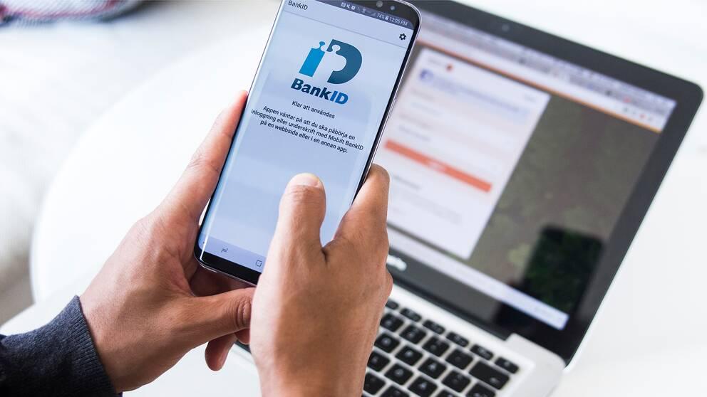 En man loggar in på sitt bank-id på mobilen
