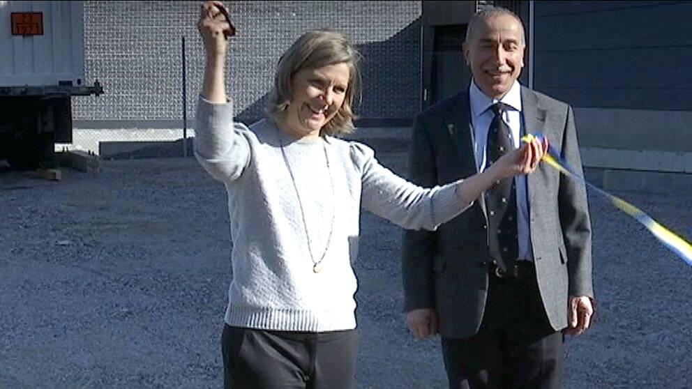 Kvinna (miljöminister) med sax i ena handen (höjd) har just klippt av blågult band. Man med slips står bredvid.