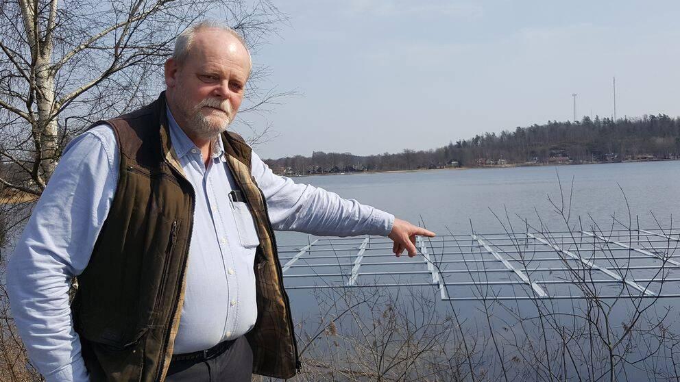 Agne Andersson pekar på plattor i sjön.