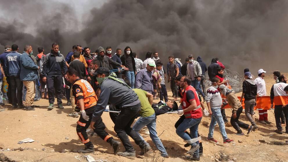 En palestinier som skadats i samband med protesterna bärs bort på bår. I bakgrunden syns svart rök från brinnande bildäck.