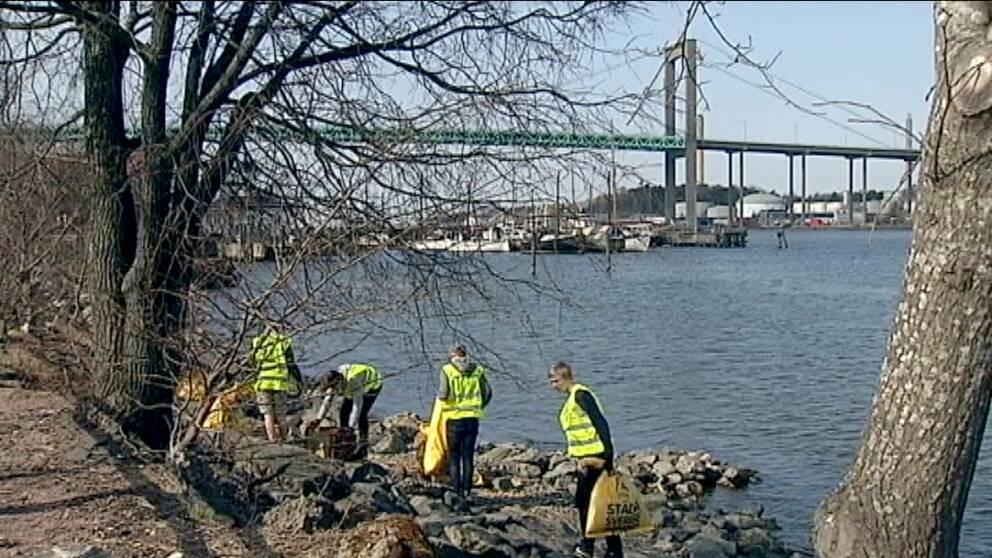 Ungdomar plockar skräp från strandkanten med Älvsborgsbron i bakgrunden.
