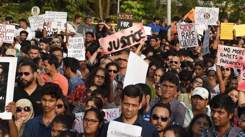 """Människor i den indiska staden Mumbai deltar i en demonstration mot våldtäkter. De håller upp plakat där det bland annat står """"Rättvisa"""" och """"Stoppa våldtäktskulturen""""."""