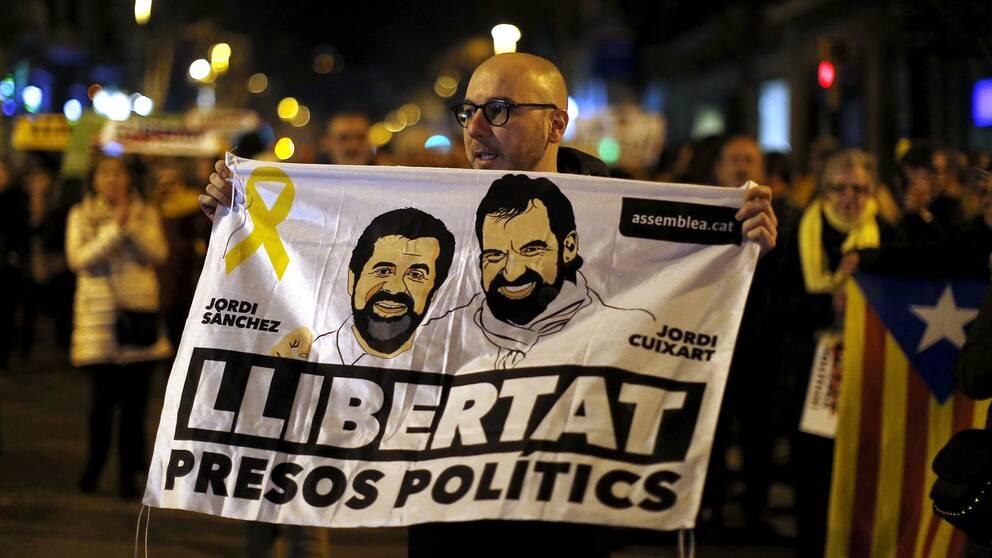En demonstrant håller upp en bild på Jordi Sanchez och Jordi Cuixart, till stöd för de två fängslade katalanska ledarna.
