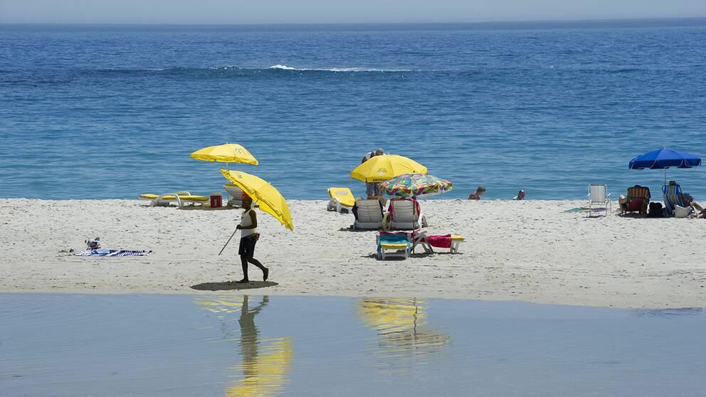 Solbad på stranden vid Camps bay i Sydafrika.