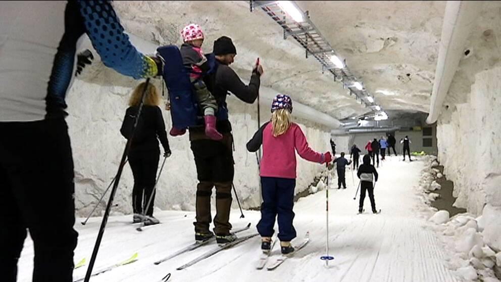 Vuxna och barn åker skidor inne i en tunnel med snö och skidspår.