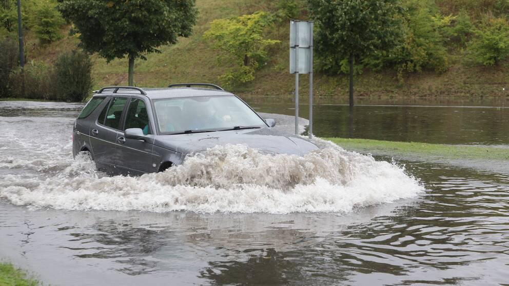 Bil kör igenom översvämmad väg.