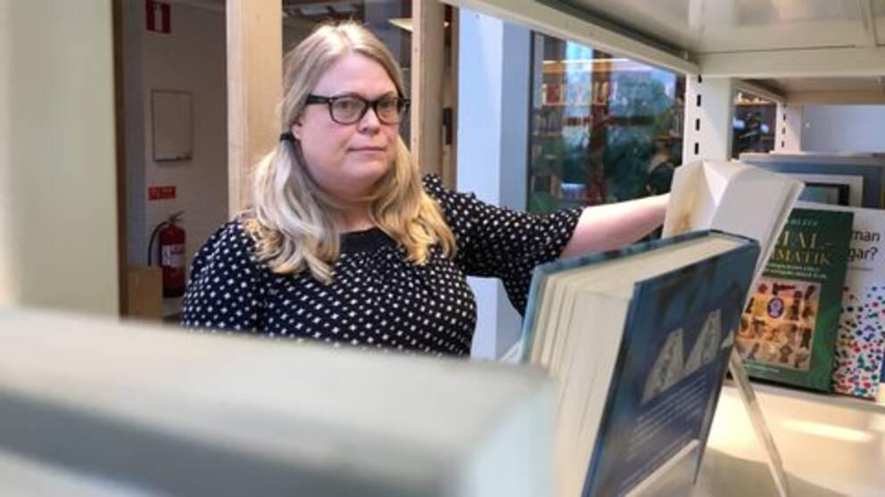 Kvinna tittar in i kameran, i förgrunden är böcker i ofokus. Bilden är tagen på ett bibliotek.