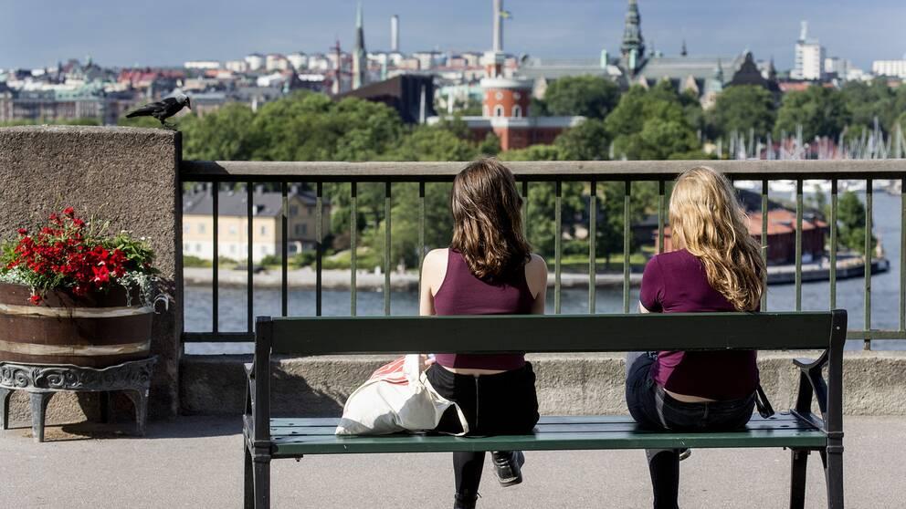 Två tjejer sitter på en bänk.