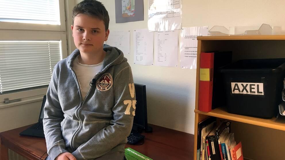 Axel Lindberg framför skrivbordet i sitt undervisningsrum.