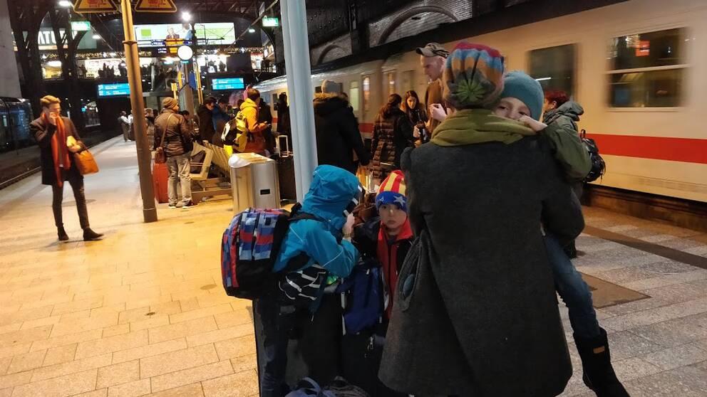 Tågperrong med Karin Sundby som står med ryggen vänd mot fotografen. I famnen har hon ett av sina barn och på marken står hennes två andra barn.