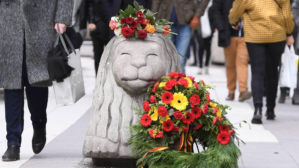 Blommor och en krans pryder ett av Drottninggatans betonglejon på årsdagen av terrordådet.