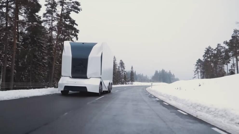 vit och svart lastbil utan förarhytt som kör på landsväg i vintermiljö
