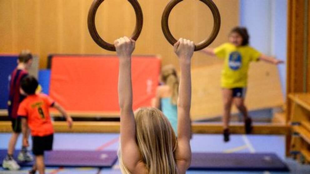 Flicka hänger i romerska ringar i förgrunden, flera barn gymnastiserar i bakgrunden i en idrottshall.