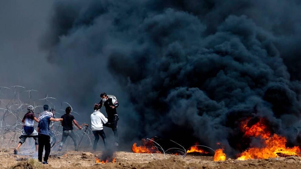 Palestinska protestanter försöker dra ner en del av stängslet vid gränsen till Israel.
