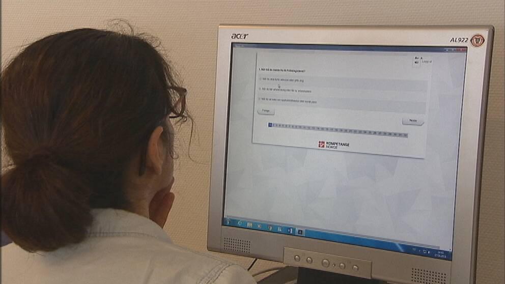 Kvinna sitter vid dator och gör Norges medborgarskapsprov.