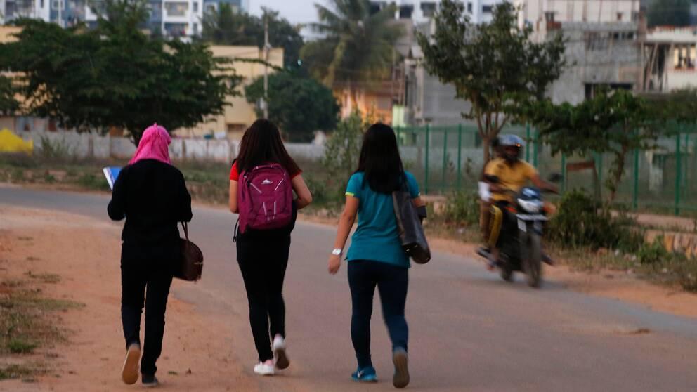 Tre flickor går på en väg och en moped med två män åker förbi.