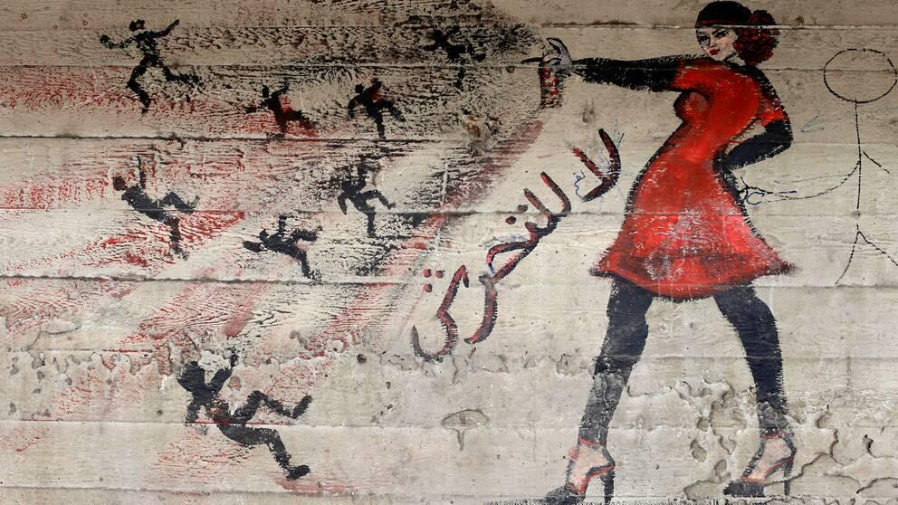 Graffitimålning i Egypten föreställande en kvinna som sprayar bort män och sexuella trakasserier.