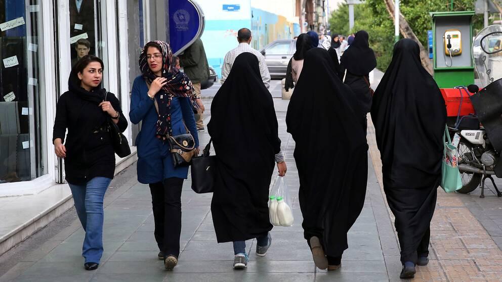 Fem kvinnor går på gatan i Teheran, Iran. Två har slöja, tre har den traditionella chadoren.